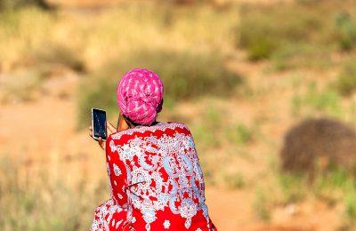 Femme africaine assise de dos avec un smartphone en main