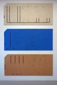 Oeuvre de Gabriel Kuri représentant trois plaquelles les unes au dessus des autres et de couleur beige, bleu et brune