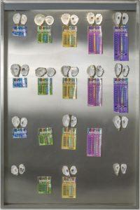 Oeuvre de Gabriel Kuri représentant une sorte de plaque en métal sur laquelle sont posées des objets ressemblant à des médailles, de différentes couleurs