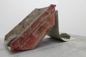 Oeuvre de Gabriel Kuri représentatn un contenair appuyé en diagonale contre ce qui ressemble à une grande feuille d'un bloc-note