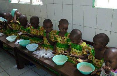 Des enfants sont alignés autour d'une table avec un bol devant eux.