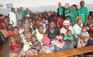 des mères avec leur enfant dans les bras sont dans une salle et attendent assises calmement