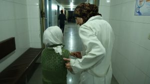 Al Ghouta, Syria - Dr Amani (R) helps a young girl into the hospital. (National Geographic)